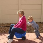 Child_pushing_grandmother_on_plastic_tricycle aging family fun