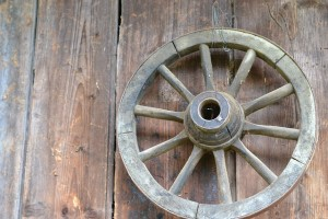 wooden wagon wheel against barn